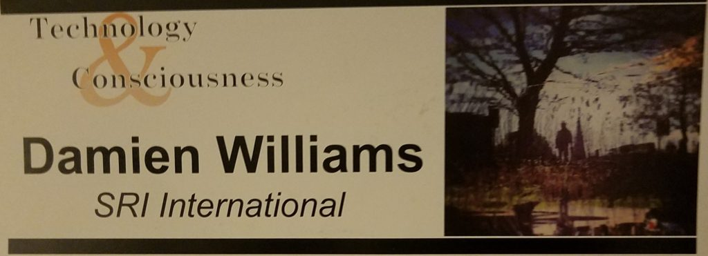 "Image of a rectangular name card with a stylized ""Technology & Consciousness"" logo, at the top, the name Damien Williams in bold in the middle, and SRI International italicized at the bottom; to the right a blurry wavy image of what appears to be a tree with a person standing next to it and another tree in the background to the left., all partially mirrored in a surface at the bottom of the image."